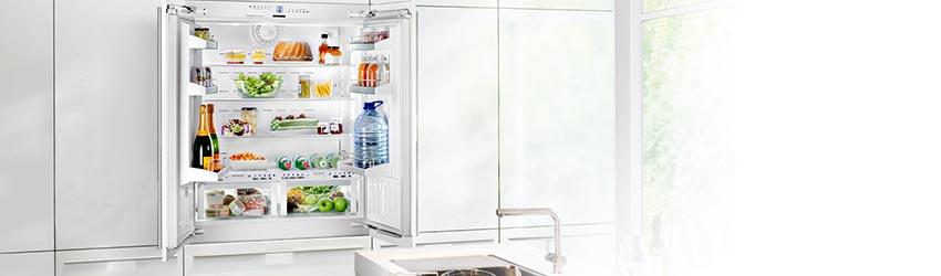 Einbaukühlschränke Kühl-Gefrierkombination weiß geöffnet mit Apfel im Vordergrund